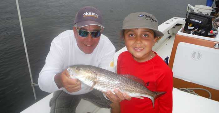 tampa fishing charters guide with child holding freshly caught refish